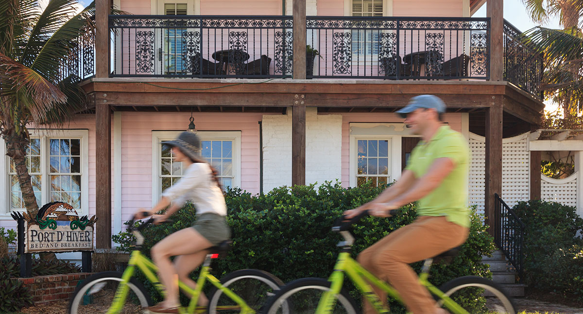 A couple bicycle past the our beachfront Florida B&B