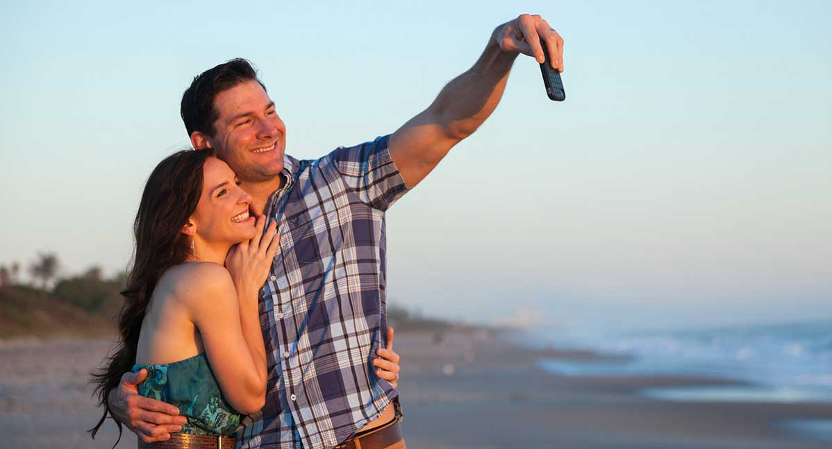 A smiling couple taking a selfie on the shore near our Melbourne Beach, FL Boutique Inn
