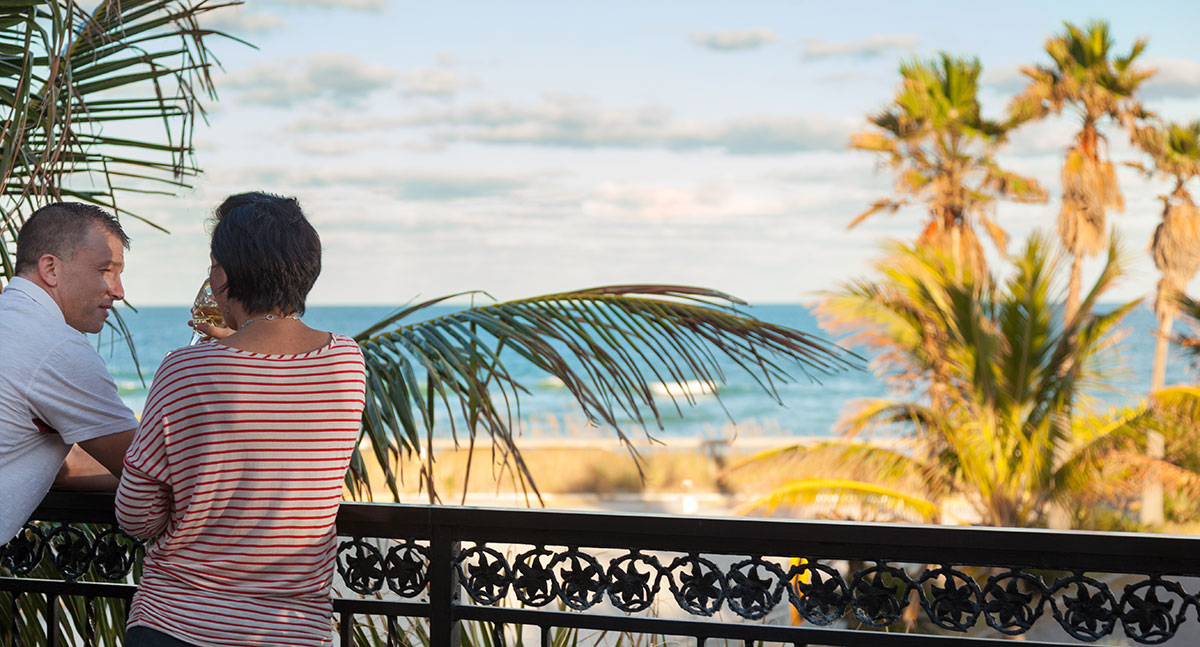 A couple standing near a railing at our Beachfront Florida Inn