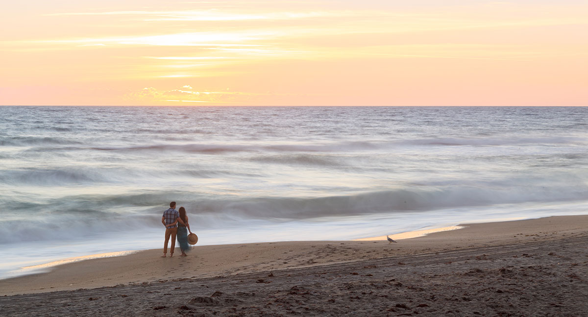 A couple stand near the ocean, not far from our Melbourne, FL boutique hotel