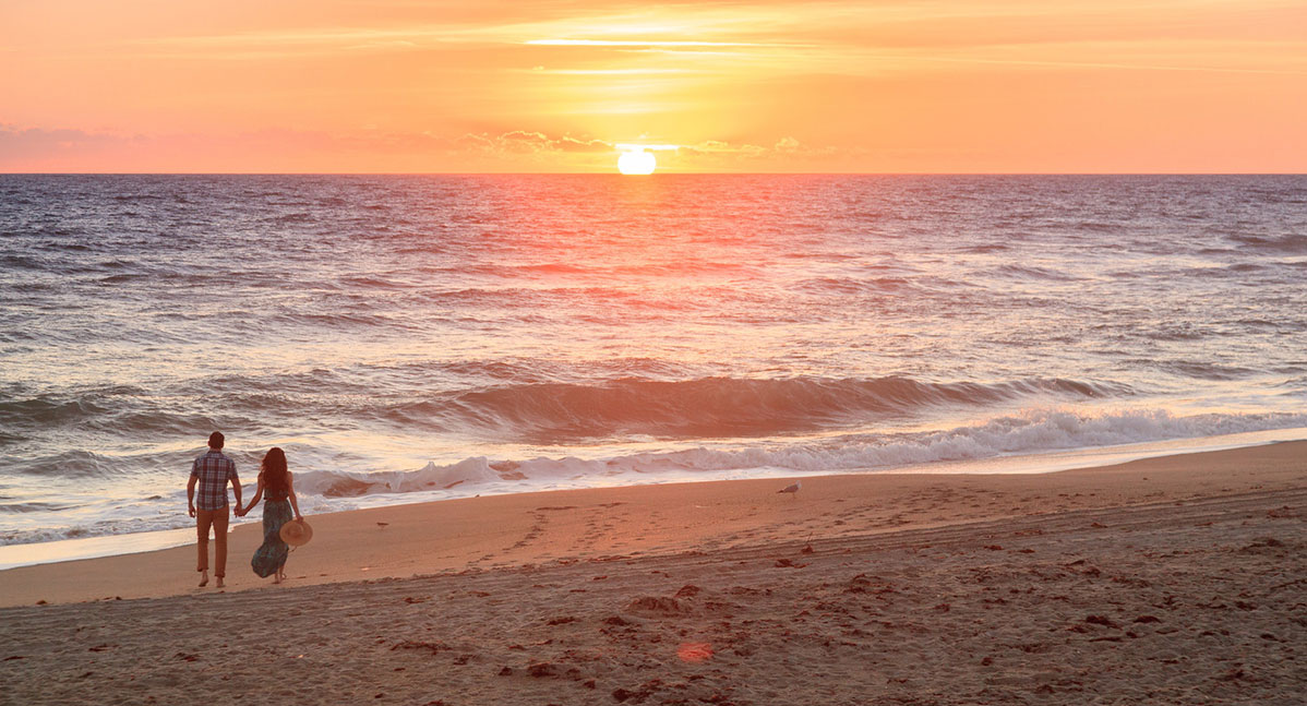 A couple stroll on the shoreline next to our Beachfront Florida B&B