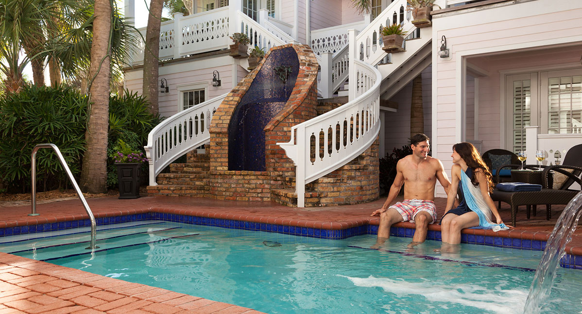 A couple sit at the ledge of the pool at our Melbourne, FL Inn
