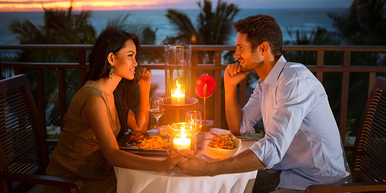 Couple having a romantic dinner with view of the ocean