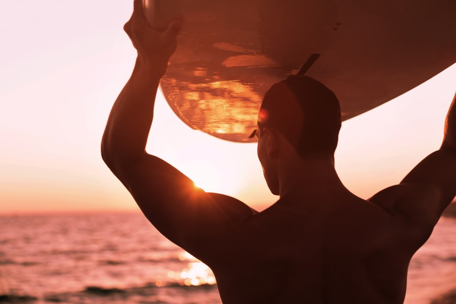 a man holding a surfboard over his head