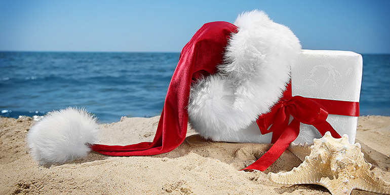Christmas present with Santa hat on the beach