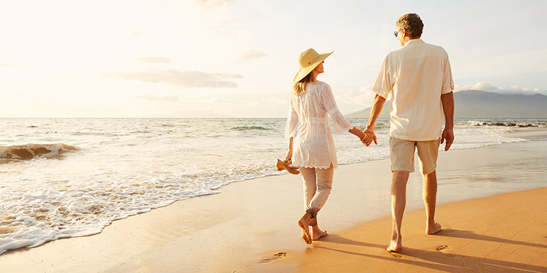 Couple walking on the beach and holding hands