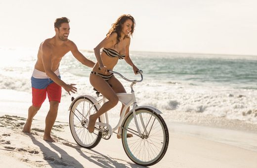 Couple riding a bike on the beach