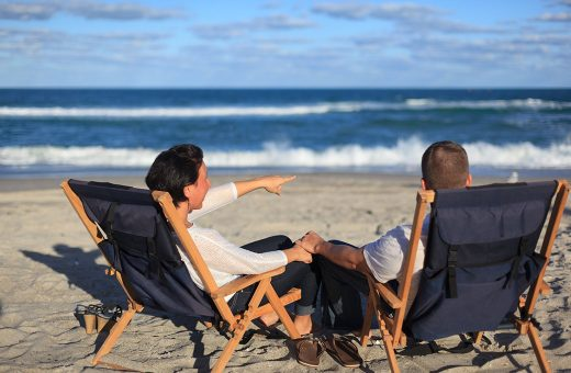 Couple sitting on chairs on the beach