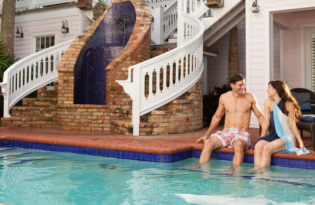 Couple sitting beside the pool