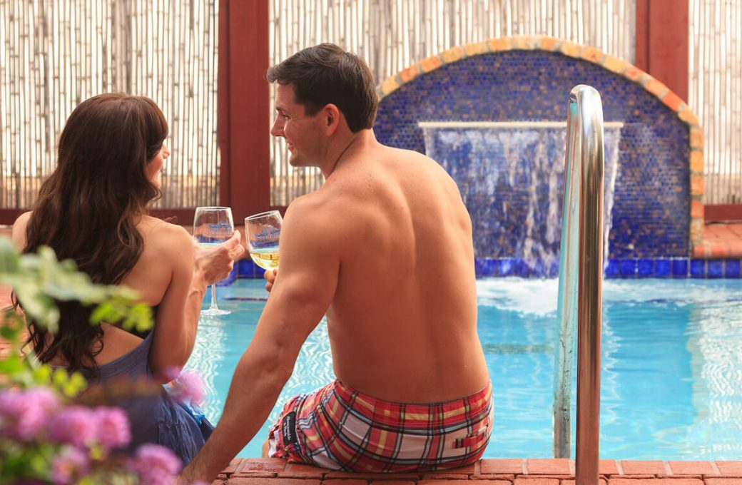 Couple sitting by the pool with wine