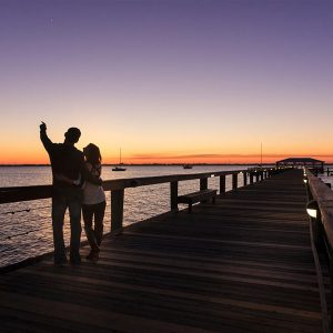 Couple walking down a boardwalk at sunset