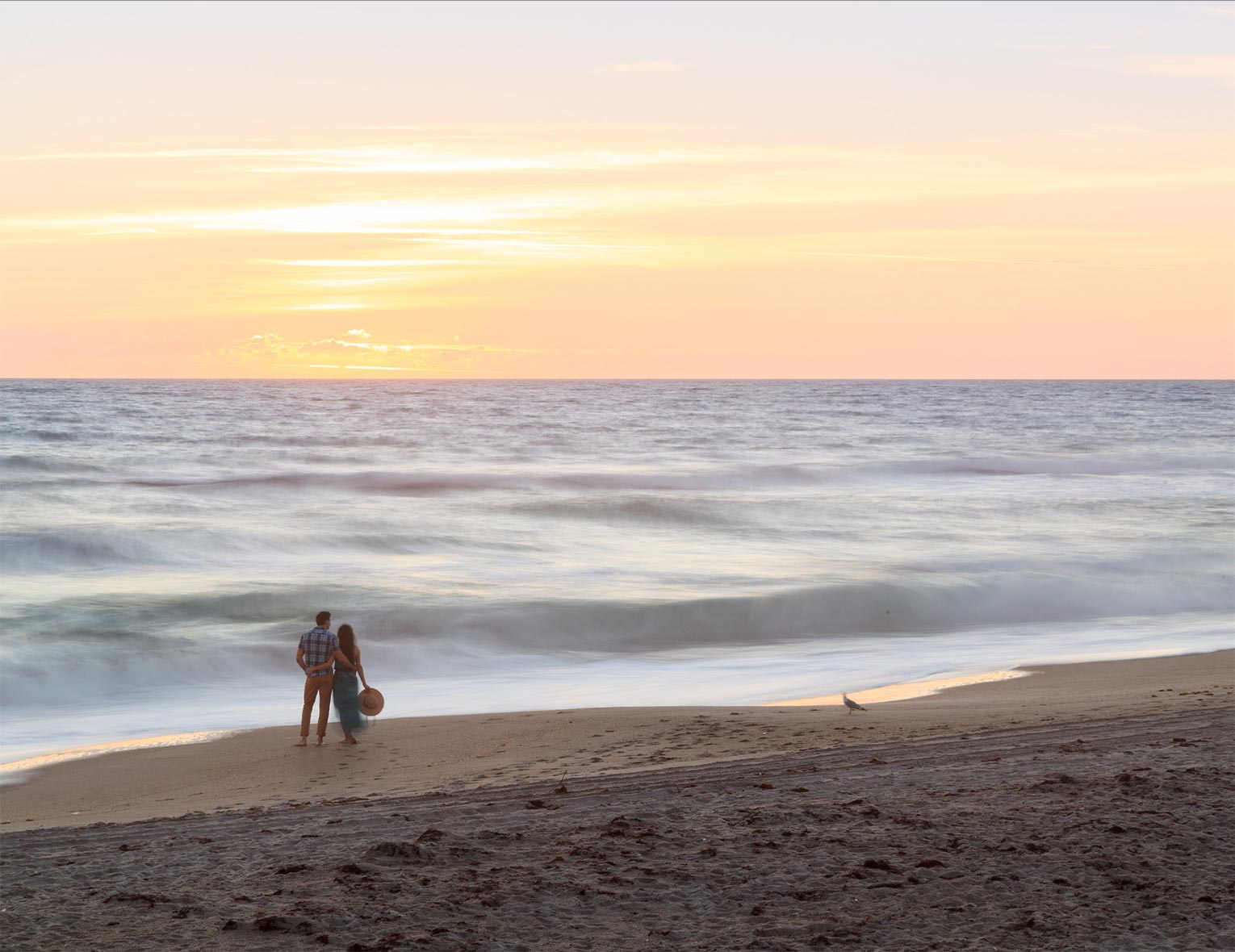 Couple looking at the ocean sunset while on the beach