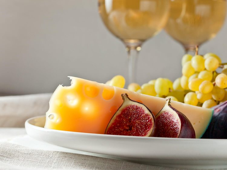 Fruit and cheese with wine glasses in the background