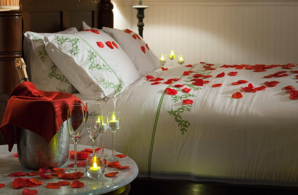 Rose petals on the bed and chilled champagne on the side table