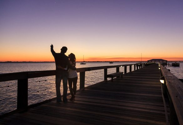 Couple on a boardwalk at sunset