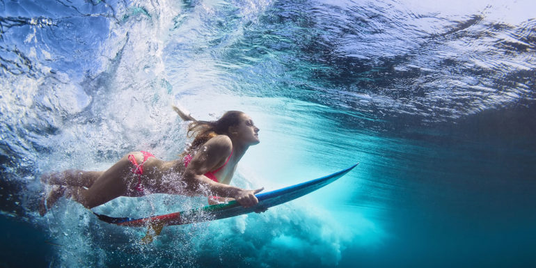 Surfer woman under the water