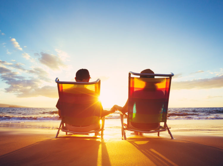 Couple sitting in chairs and holding hands on the beach