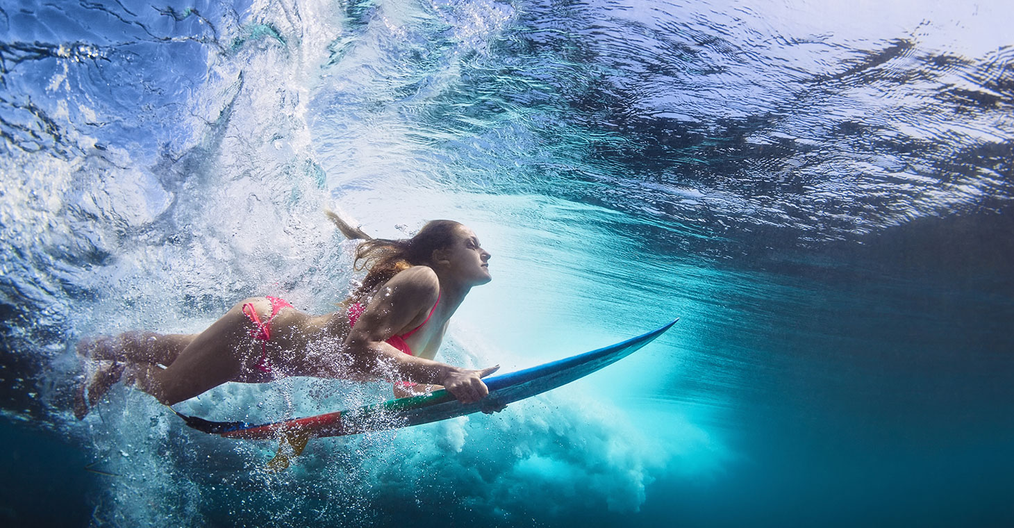 woman diving under the water while surfing