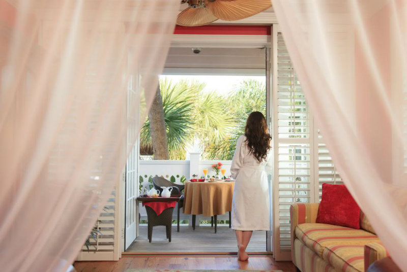 Woman in bathrobe looking out on private deck with breakfast