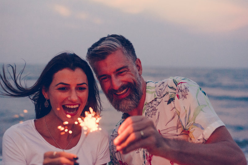 Couple celebrating their anniversary with sparklers on the beach