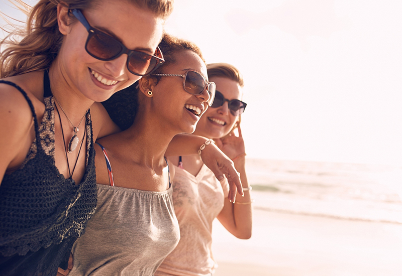 group of three girls laughing on the beach