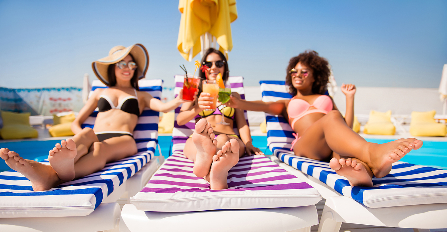 three women on the beach with drinks
