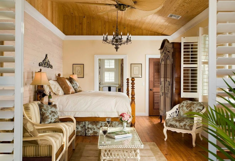 Warm guest room with wood ceiling and four-poster bed in natural tones