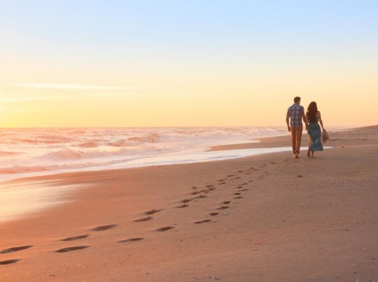 couple walking on beach near port d'hiver
