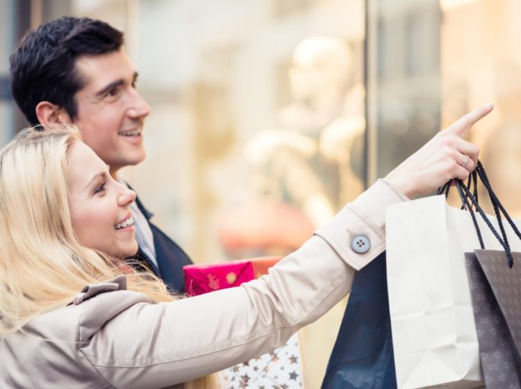 couple pointing and shopping with bags