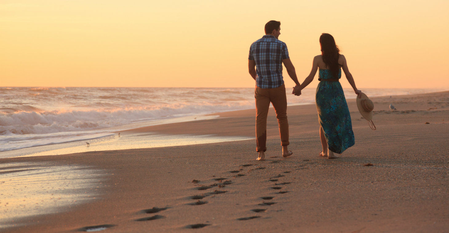 Happy couple strolling hand-in-hand on the beach