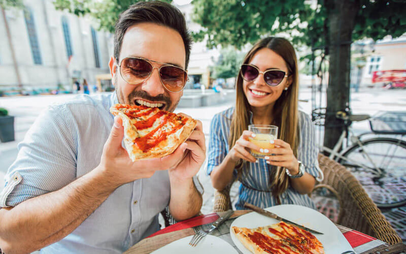 smiling couple eating pizza in Melbourne Florida