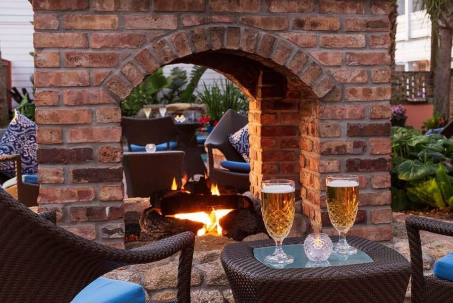 two glasses of beer by an outdoor fireplace