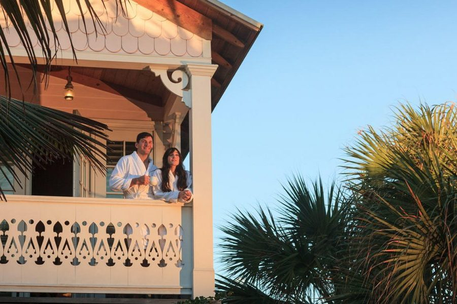 a couple watches the sunrise from their room balcony at the inn