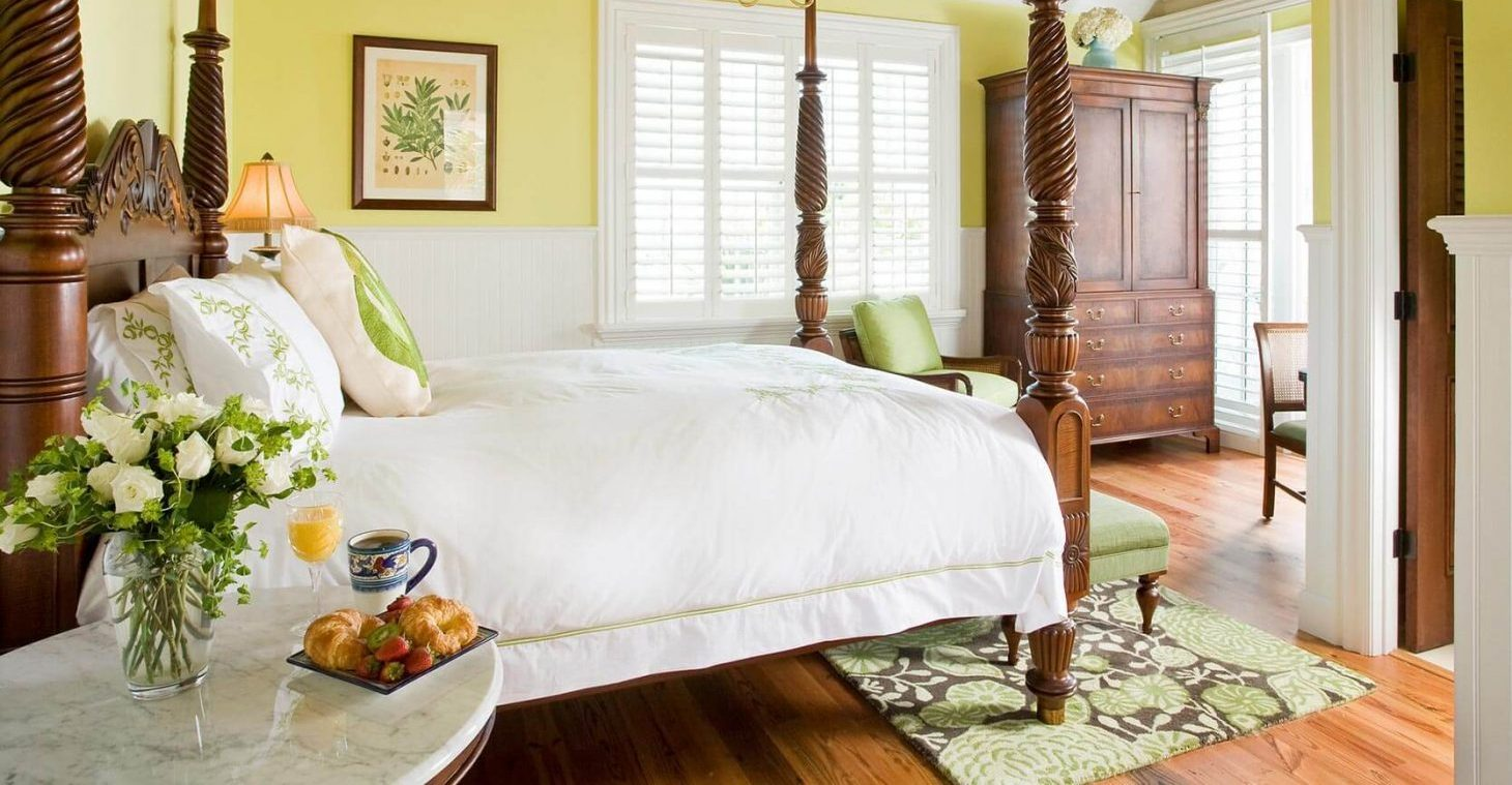Spacious and bright guest room with four poster bed and armoire