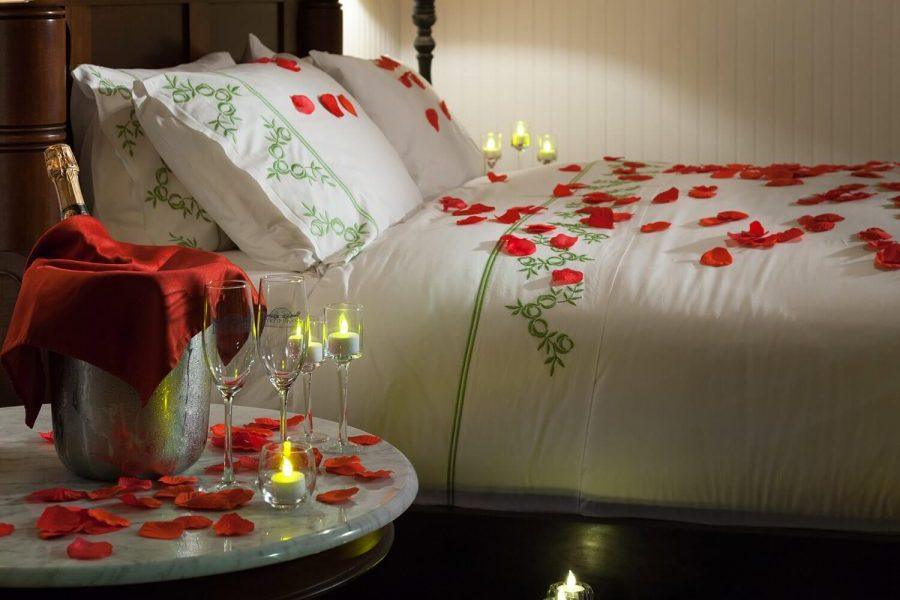 Rose petal covered bed and champagne on a romantic getaway in Florida