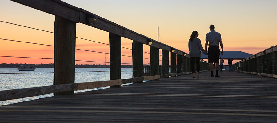 Couple strolling on a pier at sunset during Florida getaway