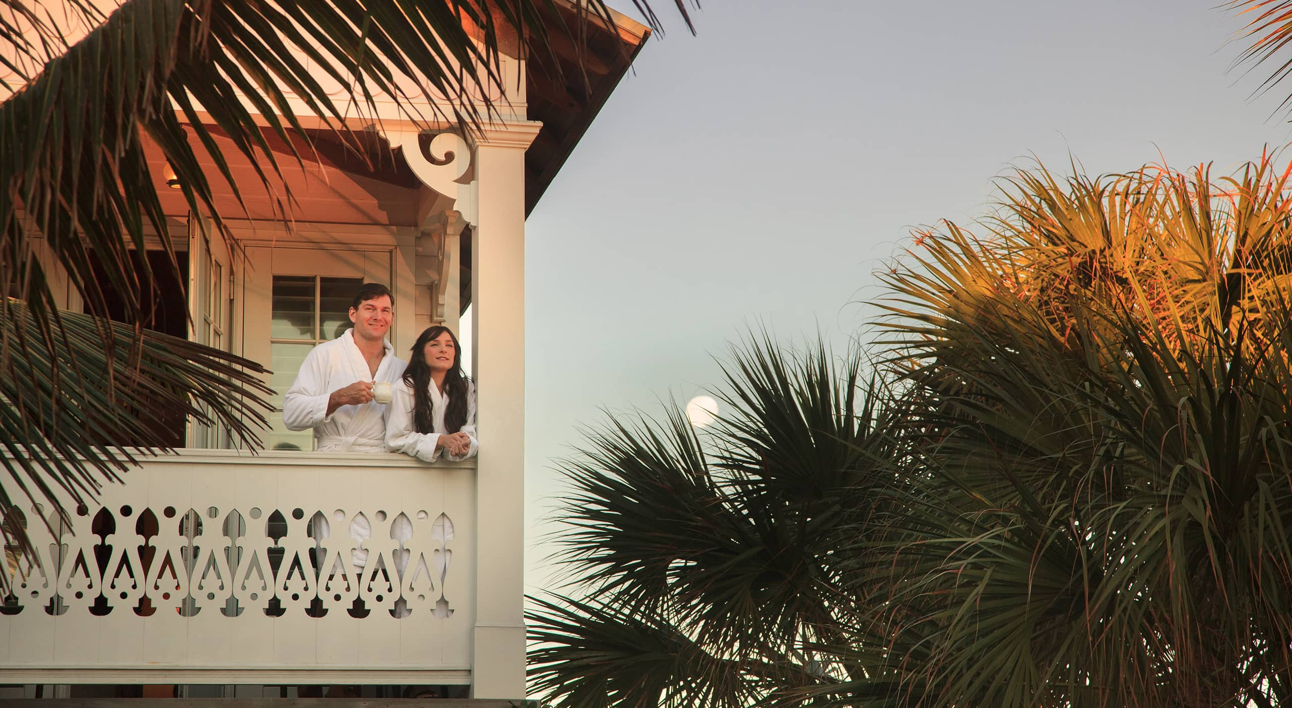 Couple with coffee on balcony at sunrise