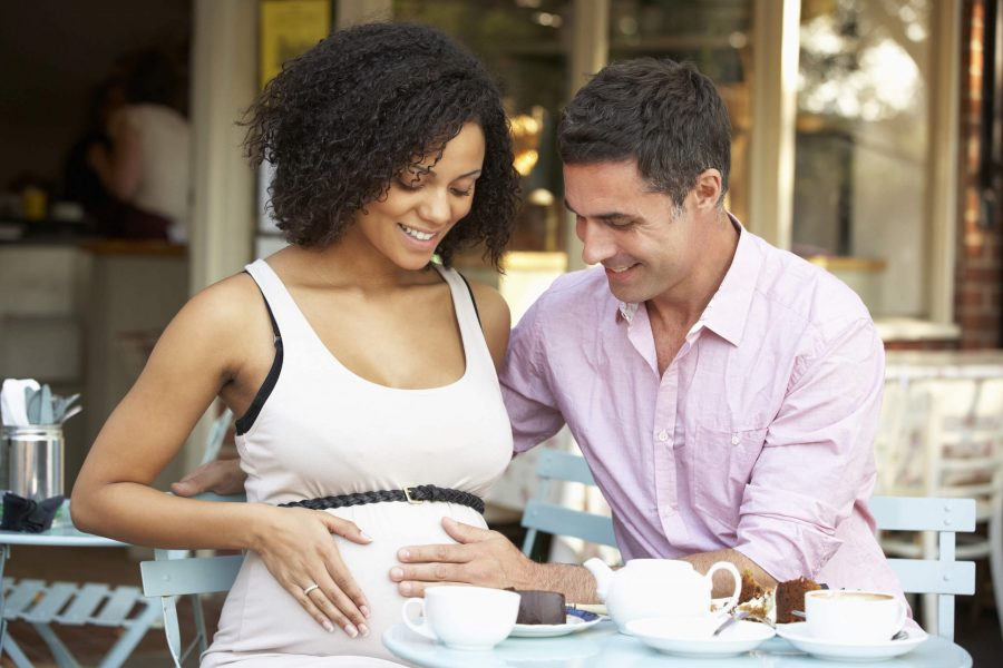 a young couple sitting at an outdoor cafe and woman is pregnant